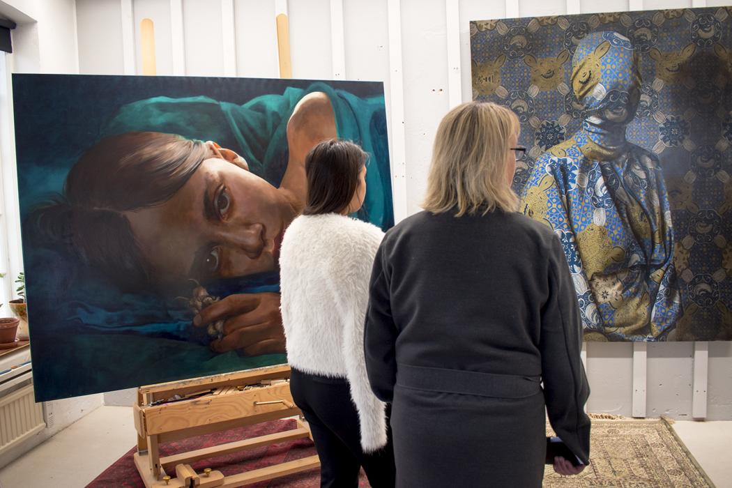 Två personer tittar på stora målningar i Markus Åkessons ateljé