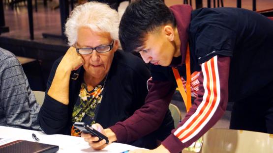 Elev står lutad över bord med en mobil och hjälper en senior