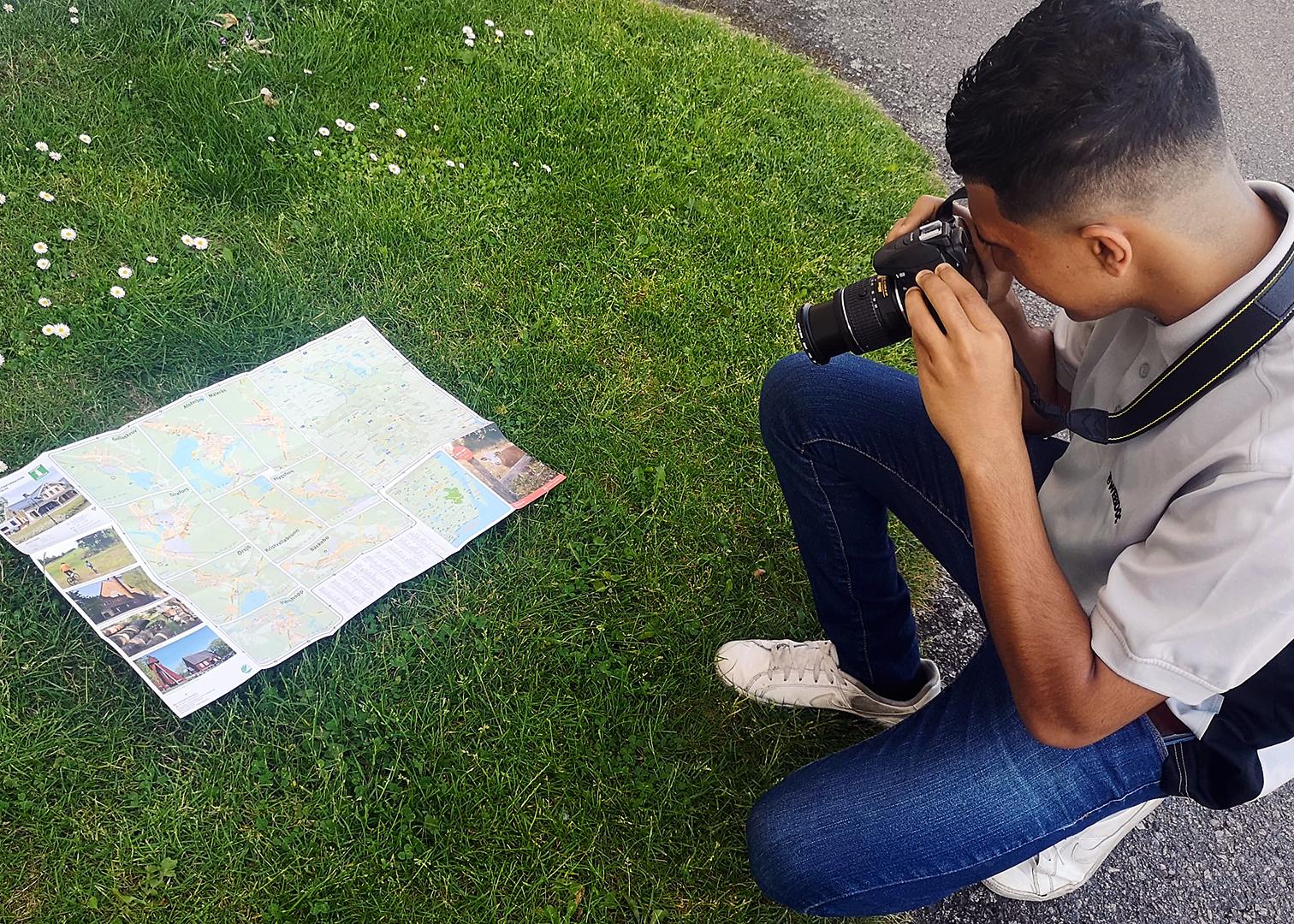 Mohannad fotograferar en karta utomhus