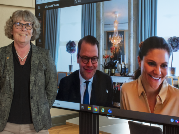 Kommunstyrelsens ordförande står bredvid en stor skärm med kronprinsessparet leendes i bild