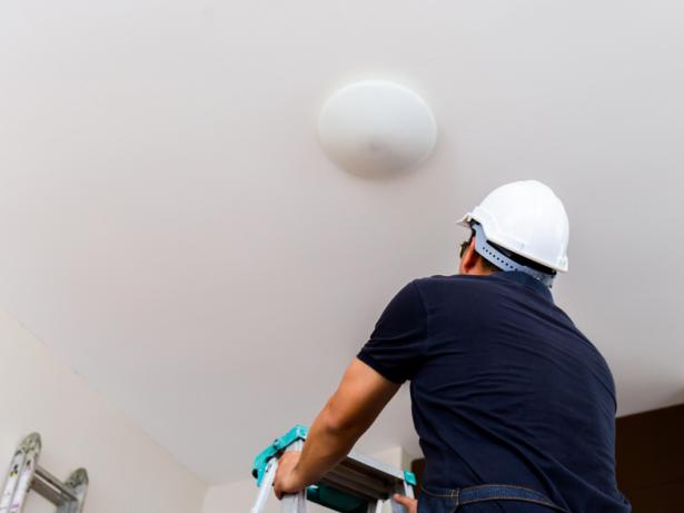 Person står på en stege och tittar upp mot en lampa i taket