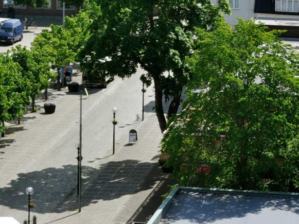 Kullerstensgata, träd och gatlyktor. Vy ovanifrån på en del av torget.