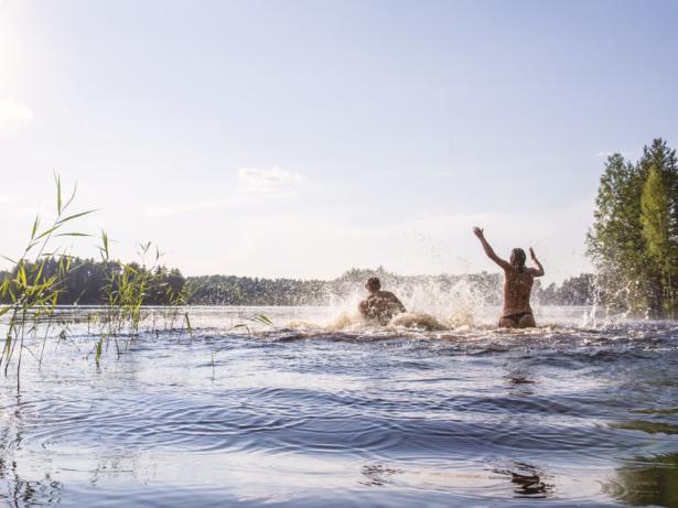 Vy över sjö. Två personer ha roligt och kasta upp vatten i luften.