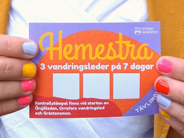 Person håller upp stämpelkort. På kortet syns tre stämpelrutor, informationstext om tävlingen och Nybro kommuns logotyp.
