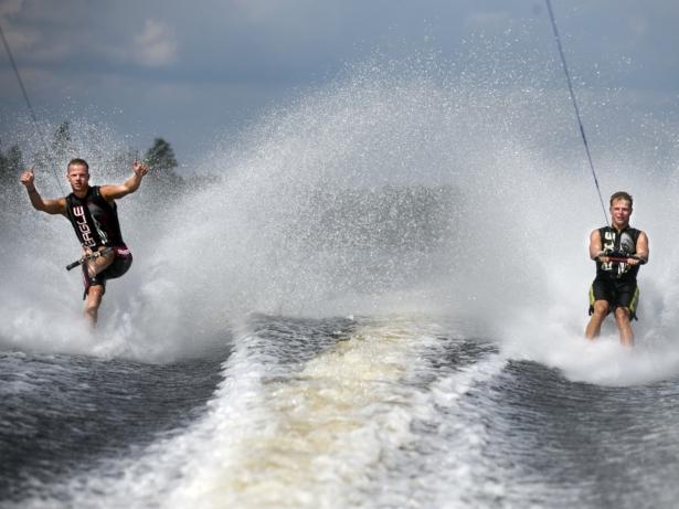 Två personer åker vattenskidor barfota