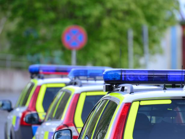 Polisbilar i rad med sirener på taket